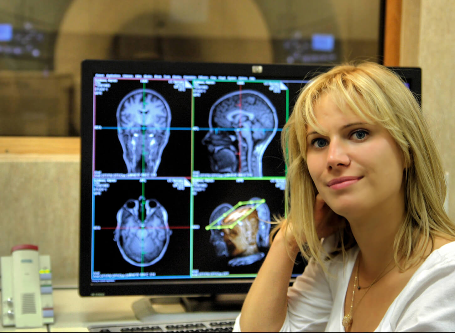 Emily Jacobs sitting in front of a computer monitor with black and white images of human brain scans.