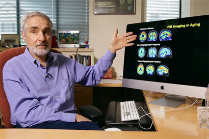 William Jagust seated at a desk, pointing to a computer monitor with images of multicolored brain scans on it.